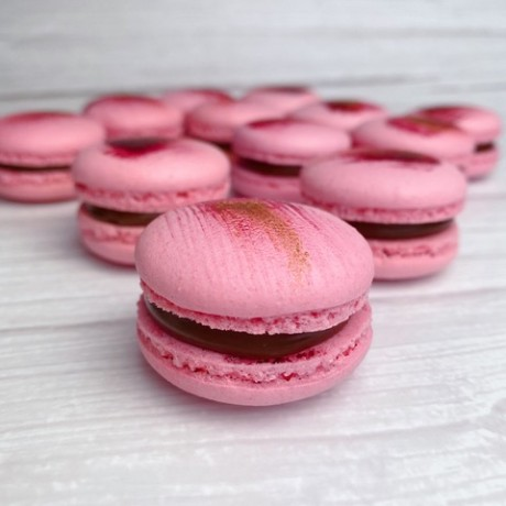 Pink French macaron cookie with a pink and rose gold decorating