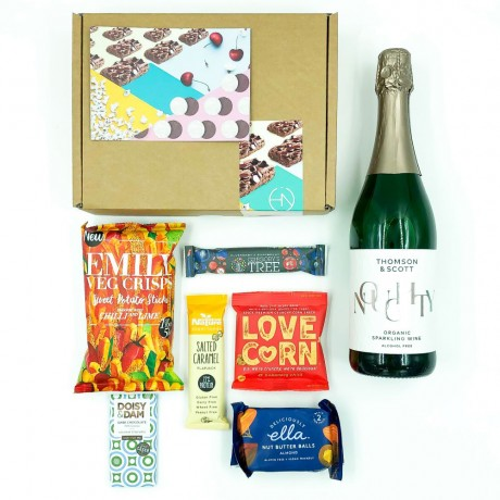 Snack box with healthy treats and a bottle of sparkling wine